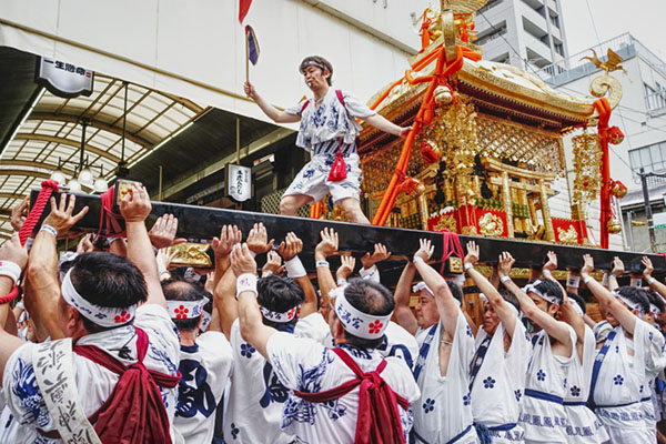 Osaka, Japan - July 25 2017: The traditional and historical Japanese festival Tenjin Matsuri in Osaka with thousands of attendants and specatators. Cloudy, but festive and colorful celebration.